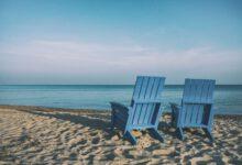 Zwei blaue Holzstühle am Strand