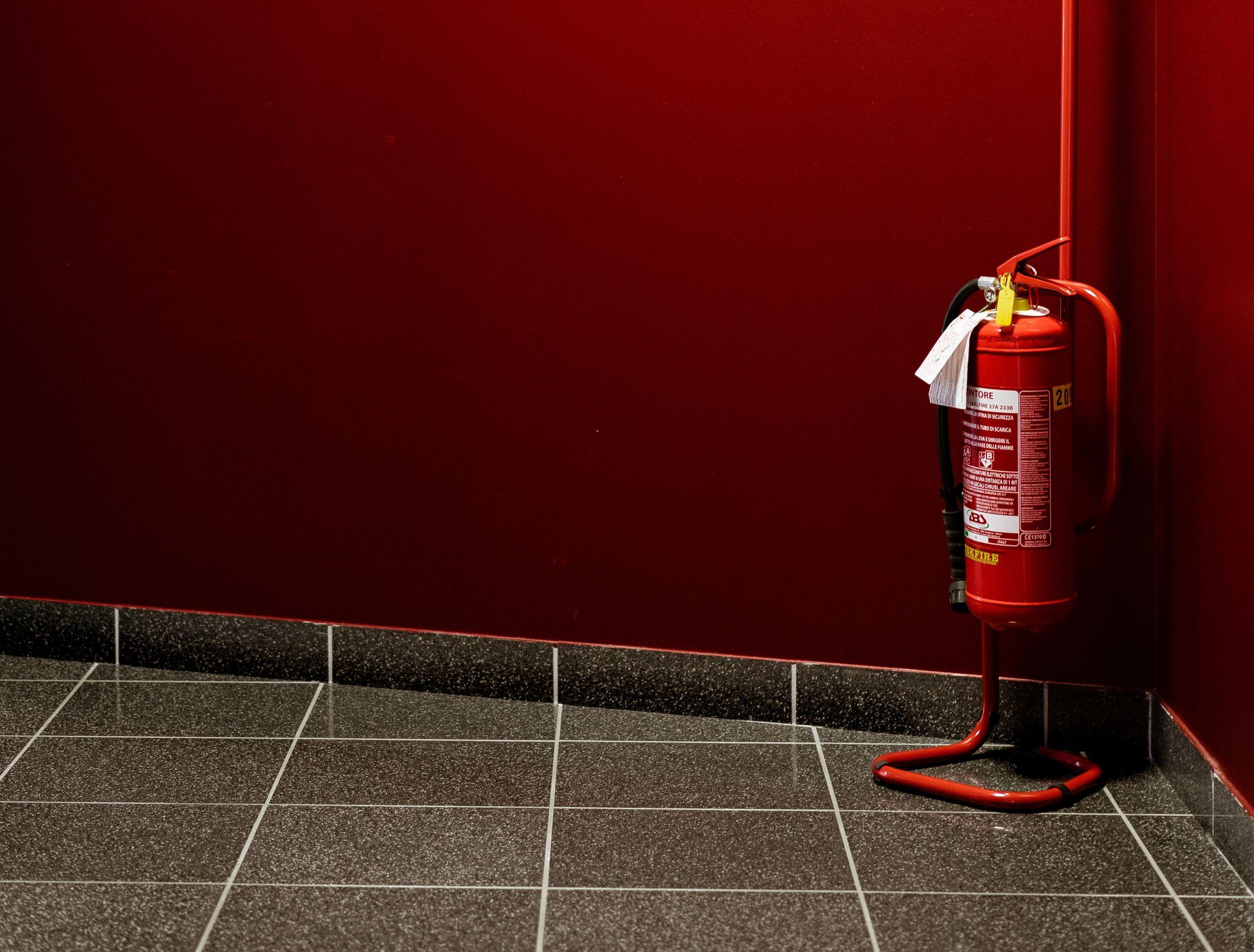 Feuerlöscher vor einer roten Wand