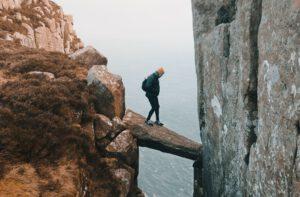 Mann wagt sich auf einen vorspringenden Felsen