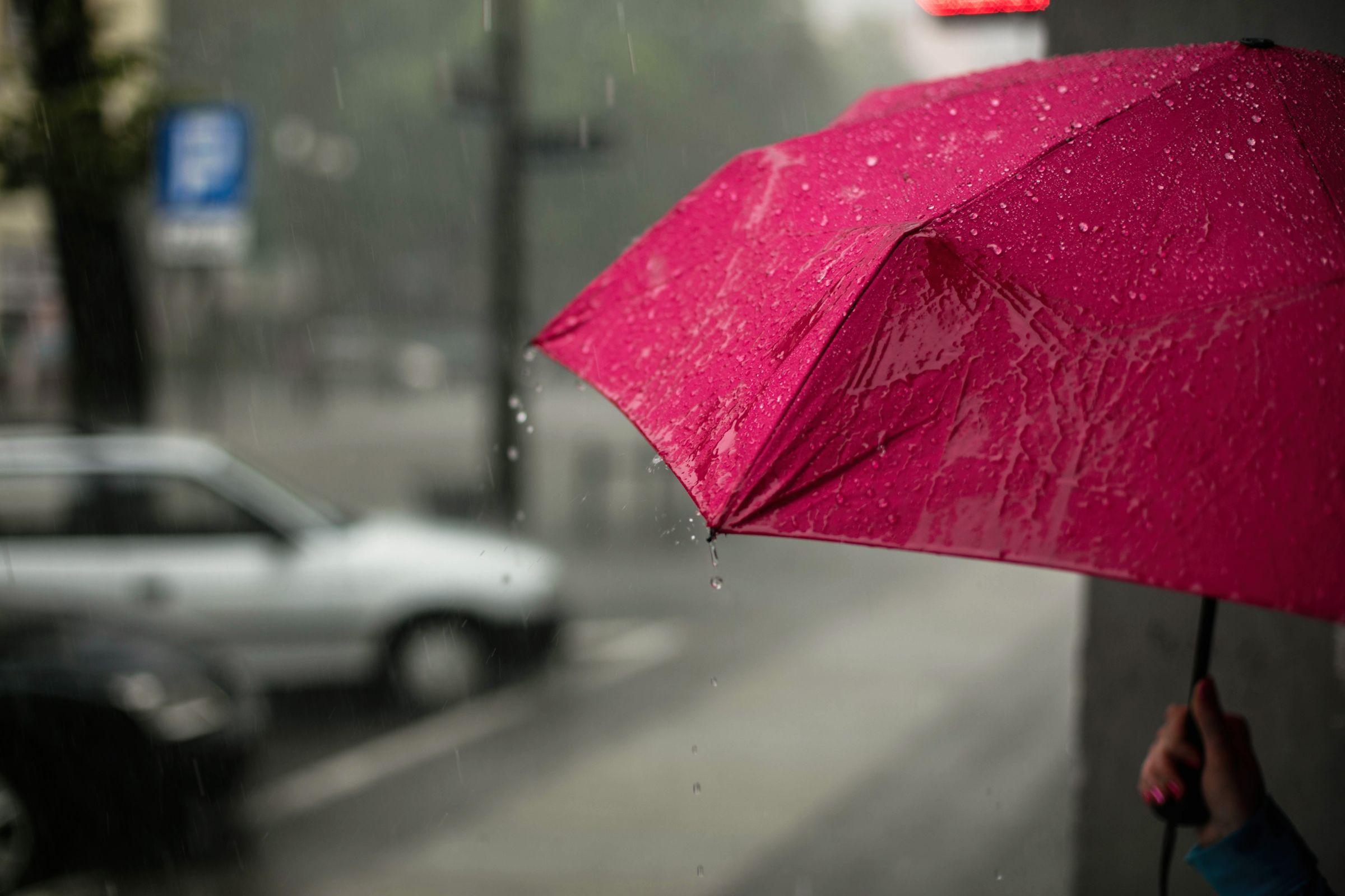 Pinker Regenschirm in einer verregneten Stadt
